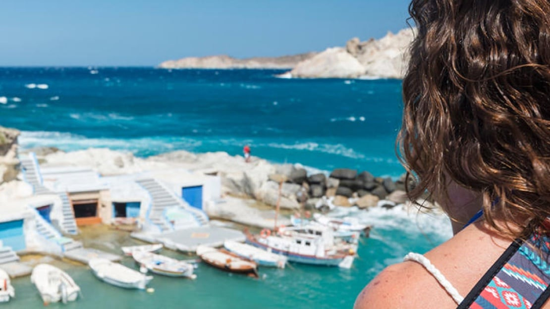 Looking over a woman's shoulder at a small port where a few small boats are moored and surround by the blue sea